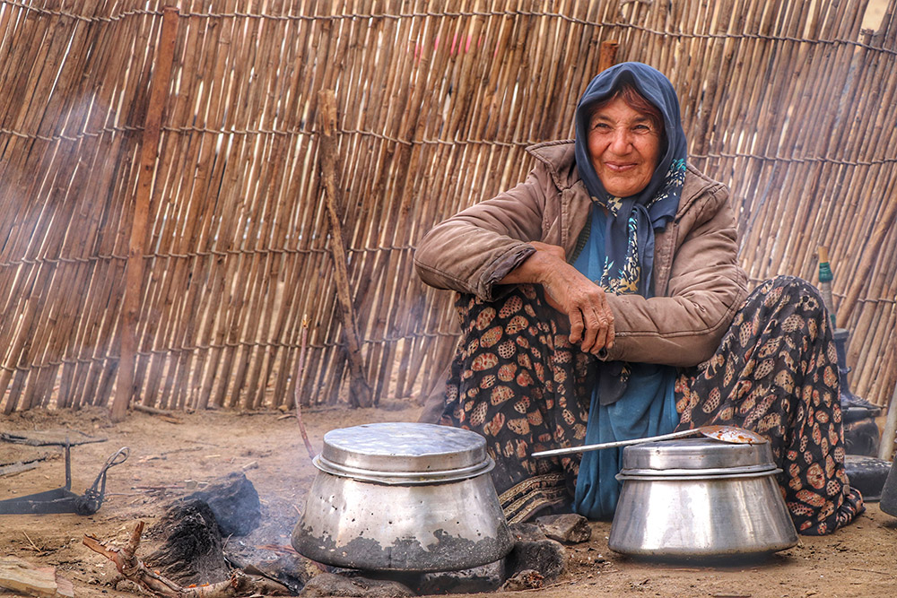 Nomad woman has a special place close to fire like the goddess of life