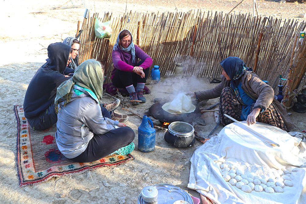 The nomad mother making bread over wood stove in pure nature of Zagros range